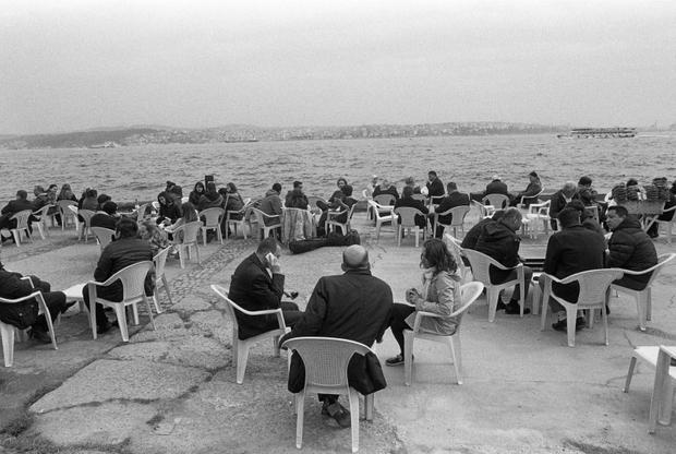 People sit on plastic chairs and drink tea near the Kabatas Ferry Docks on the Sea of Marmara.