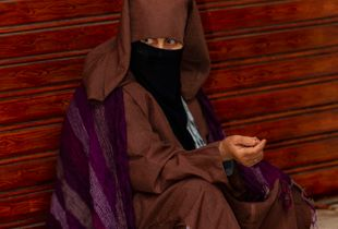 Woman wearing a hijab rests on curb