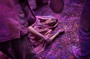 An Indian widow lies on a patio floor covered in flower petals and colored powder as she celebrates Holi or 'festival of colors' at the Meera Sahabhagini Mahila Ashray Sadam widows Ashram in Vrindavan, Uttar Pradesh, March 3rd 2015.