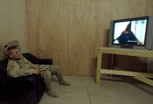 Specialist William Wimberly watches George W. Bush apologize on behalf of the US military for the torture that took place at Abu Ghraib prison. © Ashley Gilbertson