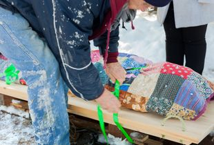 Quilt-covered body is secured to a sled for transport to the grave site.