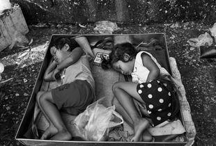 Children sleep behind the stall where their parents sell fresh vegetables in Khlong Toei market, Bangkok 2107