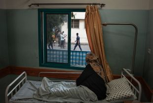 A woman, soon  due to give birth looks out the window onto the morgue from her hospital bed in Al Shifa Maternity ward in Gaza city.