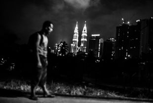 A homeless man walks to his shelter in the dead of night against the background of metropolitan city of Kuala Lumpur.