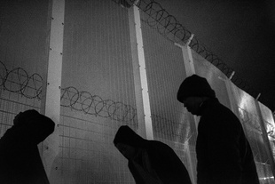 Three refugees from Eritrea wait their time to cross the fence.