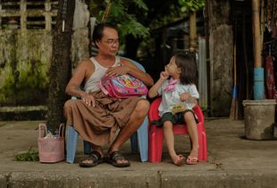 Grandfather and granddaughter waiting for school bus