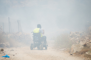 Rani Burnat is engulfed in teargas during a demonstration in Bil'in, West Bank.