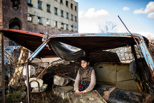"""Syuzanna (9) sitting in a """"shelter"""" made of old car rusty parts. Ten days ago Syuzanna's father committed suicide, as people say, because of debt."""