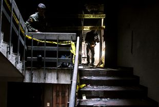 Survivors rescue their personal belongings in El Valle Building, after an airplane crashed into the building.