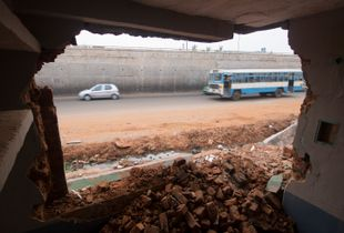 View of road traffic from inside a demolished home that was removed to make way for upcoming highway in Yelahanka, Karnataka, India