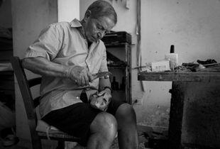 Grandad Francesco at work with his tool repairing a shoe.