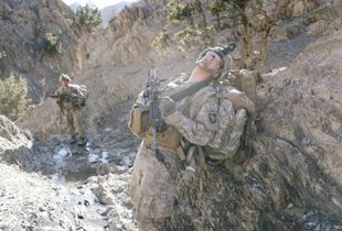 Soldiers pause briefly around hour four of an extended fourteen hour patrol through harsh mountainous terrain.