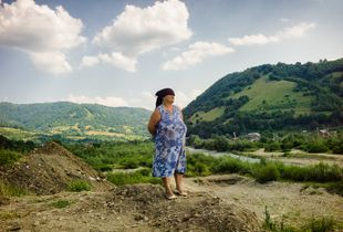 Elder woman looking over the River Viseu on the outskirts of the small village Ruscova in  Maramures.