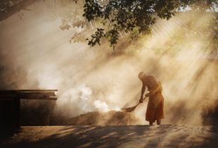 Elderly Monk Burns Leaves at his Monastery in Mae Hong Son City, Thailand.