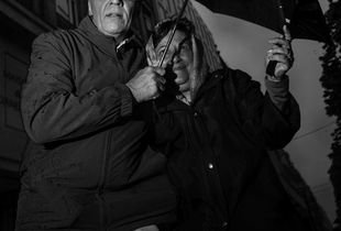 Couple fighting against rain and wind