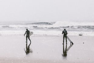 Two surfers prepare to face the freezing surf. 2013
