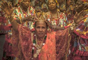 Master Bita is crowned by three Terecô priestesses during a spiritual celebration.