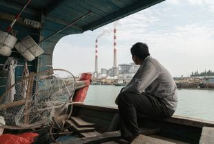 The Silent Majority 1 - A local fisherman sits at the stern of his own ship staring at a thermal plant near their estuary. Fishing activity is in a total standstill since the onset of the incident. The photo is a moment captured during our conversation.