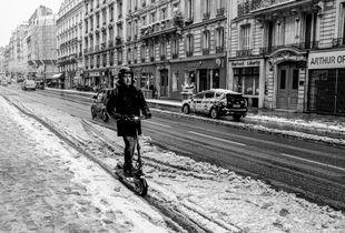 Un homme en trottinette dans Paris.