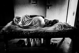 Ashram Chaitanya Vihar: a widow rests in her bed over her belongings. The only ones she have.
