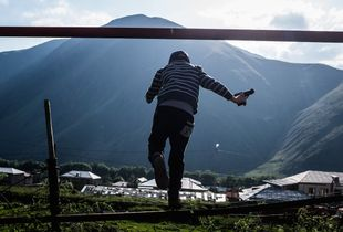 A boy plays with a toy gun in the village of Stepantsminda beneath Mount Kazbek, the mountain that separates Georgia from Russia.