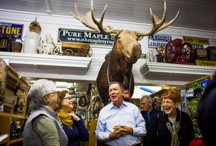 Republican presidential candidate Gov. John Kasich (center) of Ohio talks with a group of women after posing for a photo with them under a mounted moose at Fadden's General Store in North Woodstock during a campaign bus tour through New Hampshire on Wednesday, Oct. 14, 2015.