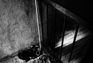 Light in the Abyss / Abby sticks and shoes are neatly arranged at the entrance of his house.