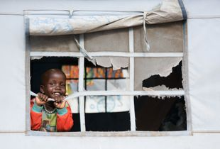 Girl, looking out of a tent in a refugee camp near Juba