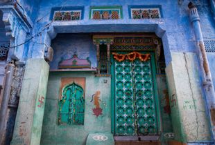 """A house in the """"blue city"""", with beautifully adorned walls and door -- colors are everywhere!"""