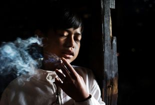 Illham Muhamad, who has smoked since he was five years old, slowly inhales his first cigarette of the day at his grandmother's home at his hillside village near Garut in West Java, Indonesia. He does not attend school and if his grandmother refuses to give him money to buy cigarettes he will cry and throw fits. © Michelle Siu