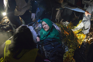 Rescue workers try to warm a Syrian woman suffering from severe hypothermia after a boat landing on Lesbos. March 20, 2016.