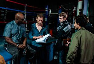 Cast & crew review the script before a scene.