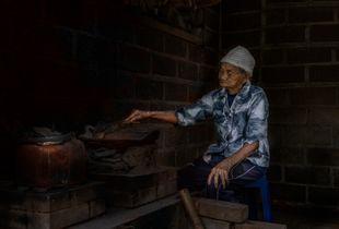 Old Woman roasting Kopi Luak