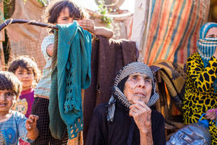 Bekaa Valley, LEBANON, September 5, 2014: Syrian refugee Aida el Issa (79, center), and her grandson Amjad (7, center left) fled from Syria over night three years ago, when news occurred that their village was going to be bombed. They don't know what happened to their house since then.