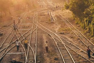 People walking on the rail tracks at sunset