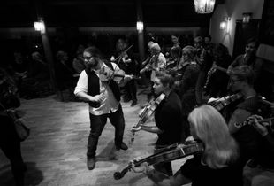 A folk music group plays in the evening to a room full of dancers.