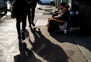 Clochard asking for money in fashion street, Milan (Italy)
