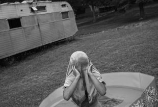 Michael, 8, plays in a kiddie pool. The first time Michael's mother used meth she went on a five day binge. On the fifth day she woke up to find her oldest son drowning in the bathtub. The boy was resuscitated, but he and Misty's other children were taken from her care. Michael is the only child who remained in her custody.