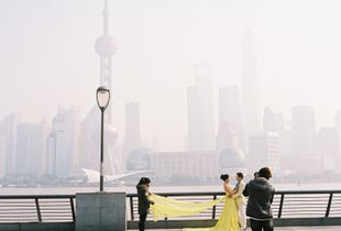 Wedding couple  photographed against a backdrop shrouded in air pollution, The Bund, Shanghai, China