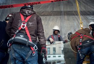 Workers getting ready to lift a glass pane.