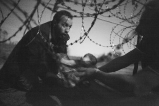A man passes a baby through the fence at the Serbia/Hungary border in Röszke, Hungary, 28 August 2015.