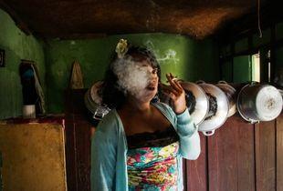 Nur smoking a cigarette in her kitchen
