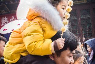 Little girl sitting on daddy's shoulder eating a quail egg