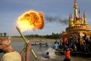 Prabaranna: Pagoda-like structures of bamboo and colored paper are lashed atop boats to make floating temples. Buddhist monks sit inside chanting sutras as the boats are pulled up and down the shallow river before thousands of onlookers. But the event is hardly solemn. The monks' chant is distorted over blaring loudspeakers, boatmen shout, and people splash in elated, sometimes drunken abandon.