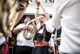 Enthousiastic Serbian dancer in traditional costume among gipsy brass band in The Guča Trumpet Festival.