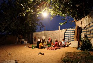 A Palestinian family which lost its home in the 2009 Israeli attack on the Gaza Strip, sitting outside their make-shift shelter, Gaza 2009.
