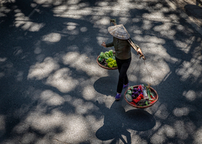 Woman in Hanoi, wandering the streets selling vegetables.