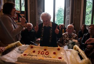 Mrs Carla Magni surrounded by her relatives and friends, stands in front of the birthday's cake to celebrate her 100 years old.
