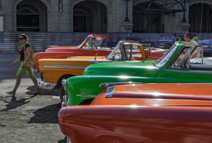 American vintage cars line up in front of the Capitolio building in Havana.