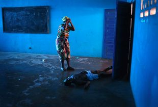 "Blue Room. Omu Fahnbulleh stands over her husband Ibrahim after he fell and died in a classroom used for Ebola patients. From the series ""Ebola Crisis Overwhelms Liberian Capital."" Winner of L'Iris d'Or, 2015 Sony World Photography Awards."